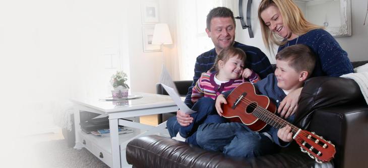 Bilde av to voksne og to barn i en sofa