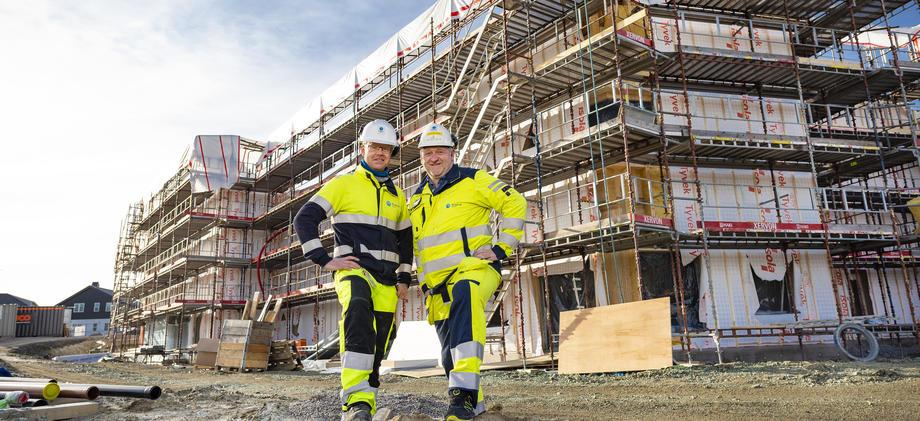 Menn i arbeidsklær foran bygg under oppføring